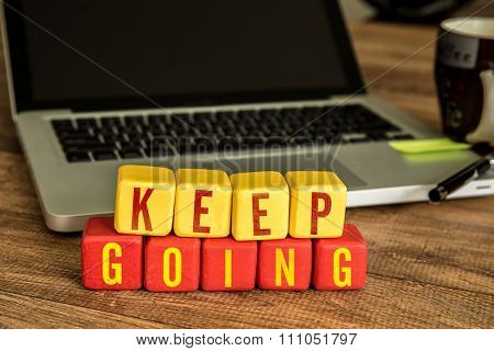Keep Going written on a wooden cube in a office desk