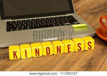 Kindness written on a wooden cube in a office desk