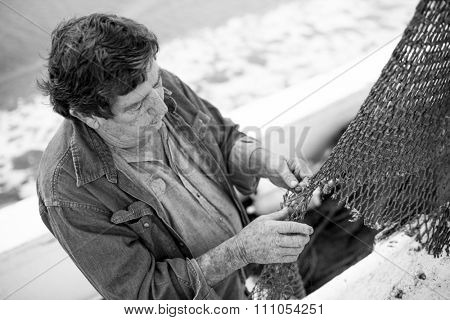 Commercial deckhand mending nets on fishing boat