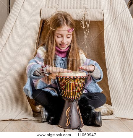 little girl with drum near wigwam playing Indian close-up