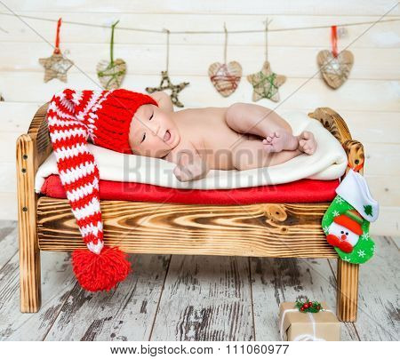 sleeping newborn baby on a cot in colorful christmas decorations