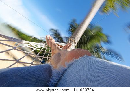 Feet of man relaxing in a hammock on beach close-up