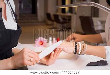 Woman shaping other woman's nails