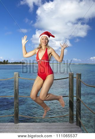 The woman in New Year's Santa-Klaus cap on background of sea jumps