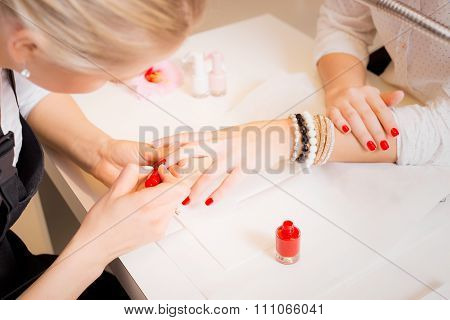 Manicure specialist painting clients nails red