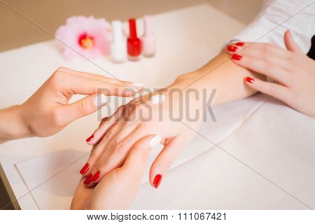 Woman massaging woman's hands after manicure