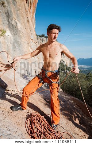 Rock Climber Collecting Belay Rope Over The Mountains
