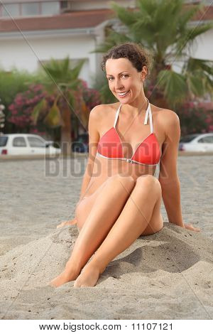 Young Woman In Orange Bikini Sitting On Beach And Smiling, House And Palms