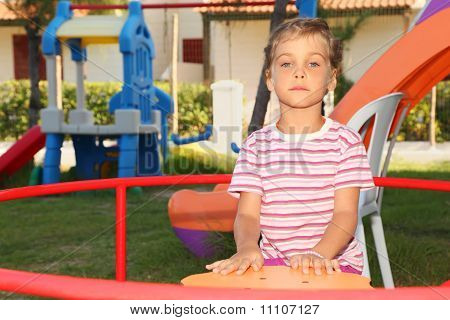 Serious Little Girl In Pink Shirt Sitting On Merry-go-round On Playground And Looking At Camera