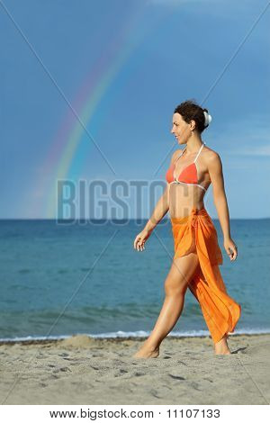 Young Brunette Woman In Orange Bikini And Pareo Walking On Beach And Smiling, Rainbow
