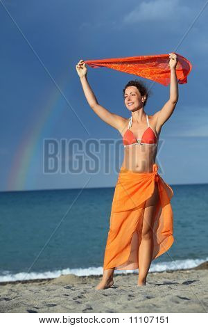 Young Brunette Woman In Orange Bikini And Pareo Holding Scarf Over Her Head And Smiling