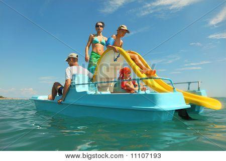 Família feliz com menino e menina no pedalinho com corrediça amarela no mar, vista da água