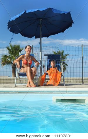 Young Mother In Orange Bikini And Daughter Sitting On Beach Chair Near Pool And Smiling