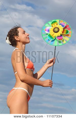 Young Beauty Woman In Orange Bikini Standing And Holding Pinwheel Toy, Looking On It And Smiling