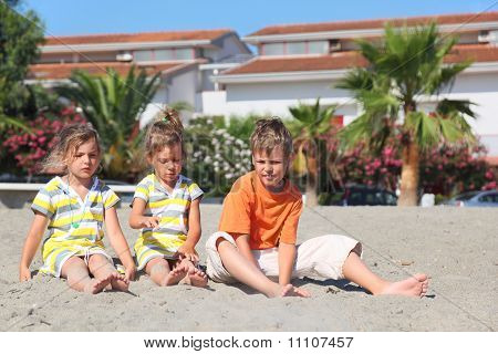 Little Boy And Two Girls Sitting On Beach, Palms And Building