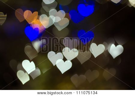 White, blue and orange hearts bokeh blur lights.