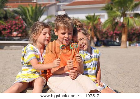 Little Boy And Two Girls Sitting On Beach And Holding lollilops