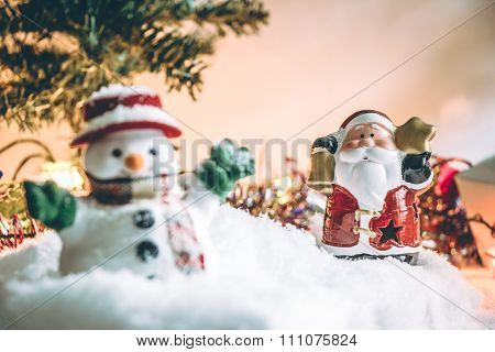 Snowman and Santa claus hold bell among pile of snow at silent night with a light bulb, light up the