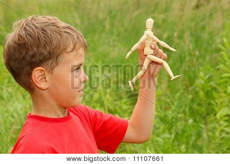 Boy In Red T-shirt Is Played By Wooden Little Manikin In Nature. Manikin Goes. Focus On Manikin