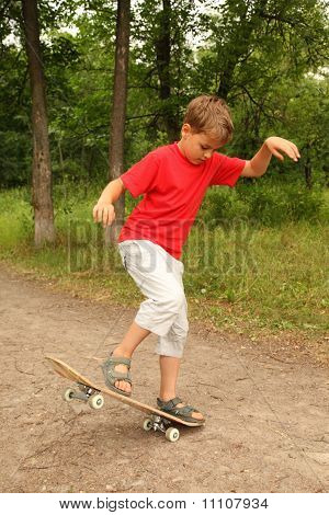 Little Boy In Red Shirt And White Shorts To Skateboard In  Forest  On Nature