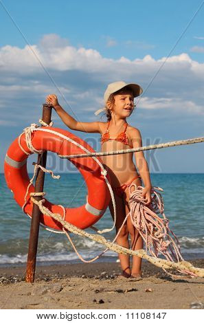 Beautiful Little Girl In Bathing Suit And Cap Standing On Beach. Girl Holding Rope.