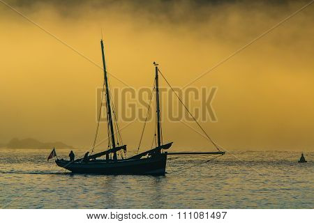 Ketch sailing boat heading out to sea