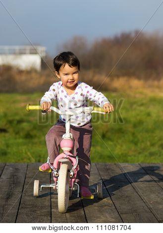 Little Girl On A Bike Near The House