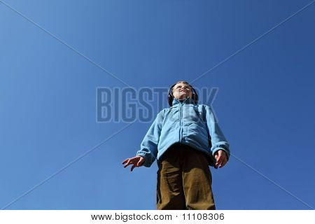 Little Boy In Blue Jacket And Big Black Headphones Listens To Music