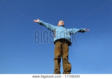 Little Boy In Blue Jacket And Brown Pants Raises His Arms To Blue Sky