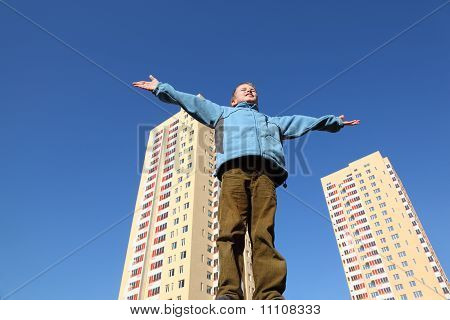 Little Boy In Blue Jacket Raises His Arms To Blue Sky. In Background Two Multi-story Yellow Houses