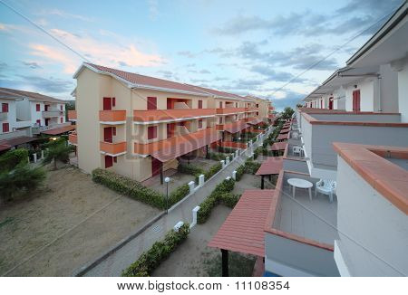 View Of Resort On Coast. Orange-storey Villas With Private Balconies