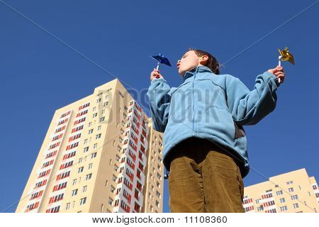 Little Boy In Blue Jacket Blowing On Pinwheels In His Hands. In Background Of Multi-storey House