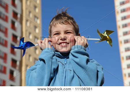 Little Boy In Blue Jacket With Pinwheels In His Hands. In Background Of Multi-storey Yellow House
