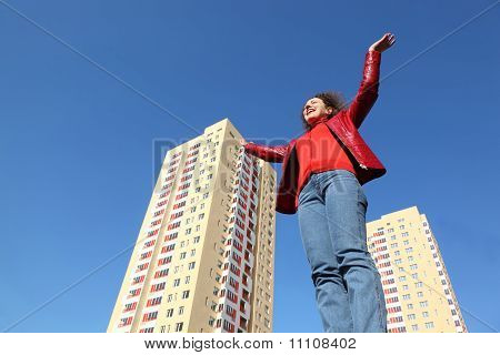 Beautiful Young Woman In Red Jacket And Blue Jeans Raises His Hands To Sky.