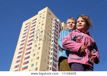 Brother Hugs Little Sister. Girl In Pink Jacket, Boy In Blue Jacket. Yellow Multi-storey Building