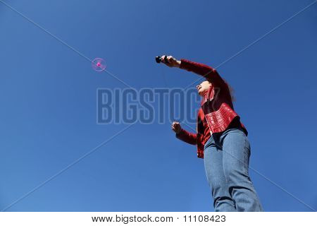 Beautiful Young Woman In Red Jacket And Blue Jeans Playing With Pink Propeller
