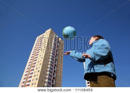 Kleiner Junge In blauer Jacke spielen mit Ballons In Form von Globe, mehrstöckige gelbes Haus