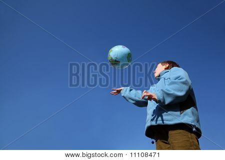 Little Boy In Blue Jacket Playing With Balloon In Form Of Globe