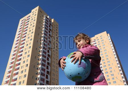 Little Girl In Pink Jacket Holds In Her Hands Balloon In Form Of Globe, Multi-storey Yellow House