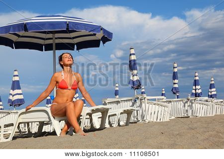 Beautiful Young Woman In Bathing Suit Sitting On White Chaise Lounge And Sunbathe