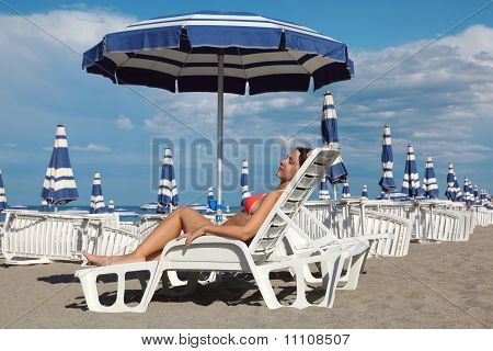 Beautiful Young Woman Lying On Lounger Under Beach Umbrella And Sunbathe.