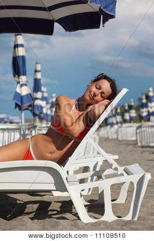 Beautiful Young Woman Lying On Lounger Under Beach Umbrella And Sunbathe.