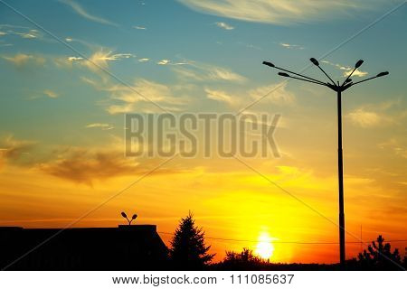 Silhouette Of A Streetlamp Against Backlight On Sunset Background
