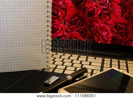 Office Workplace With Notebook, Smart Phone, Pen, Flash Drive And Wordpad With Roses Background