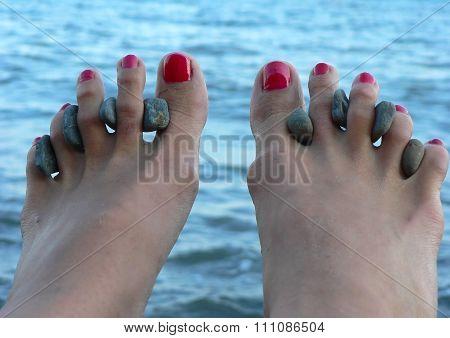 Female Legs On Sea Procedures With Curative Stones Between Fingers