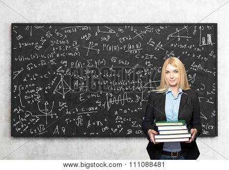 Girl With Book In Front Of Blackboard