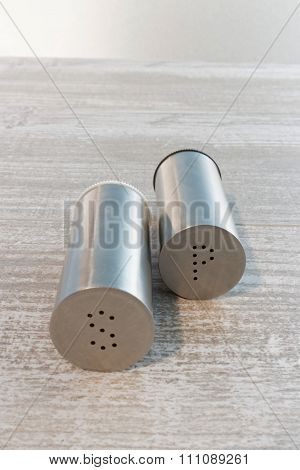 Stainless steel salt and pepper shakers on wooden table