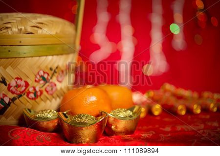 Chinese new year festival decorations, gold ingot and mandarin orange on red glitter background.
