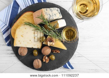 Served wooden table with wine and different kinds of cheese and nuts on the round board