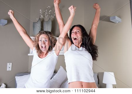 Two Attractive Women Sitting In Bed And Cheering